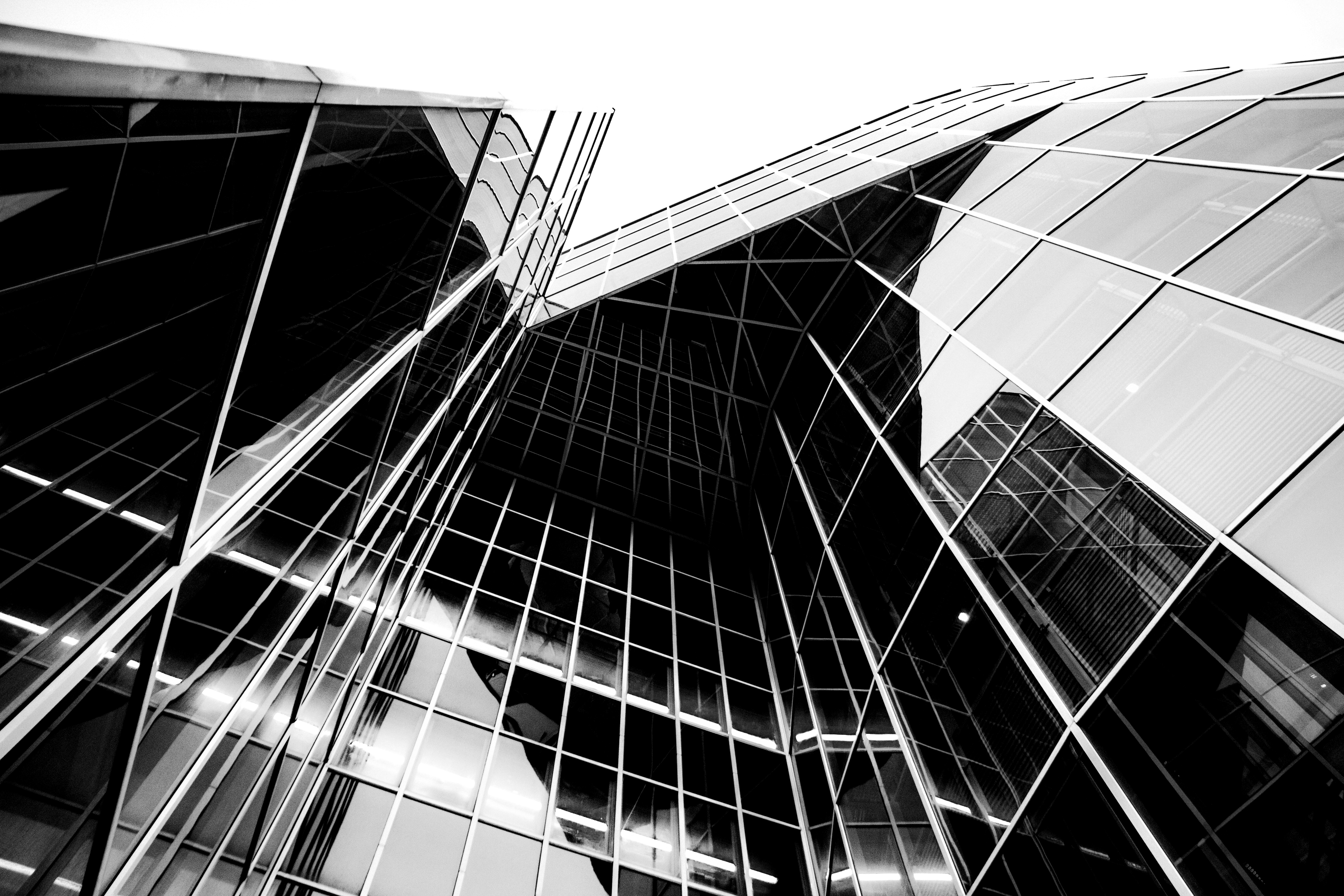 building glass architecture skyscraper windows rise facade monochrome structure shape line low angle headquarters symmetry perspective shot metropolis innovation pattern