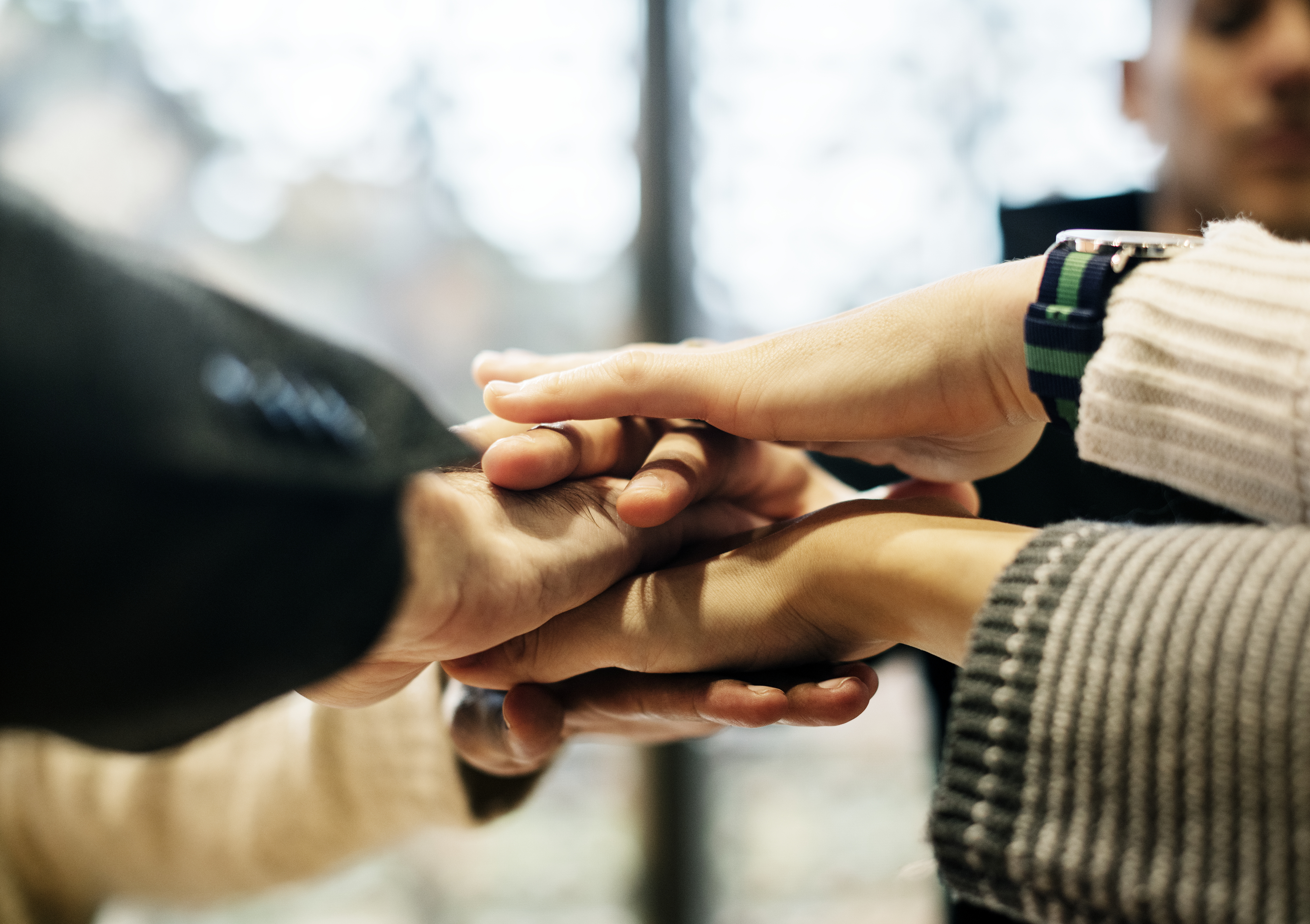 Diverse people stacking hands together